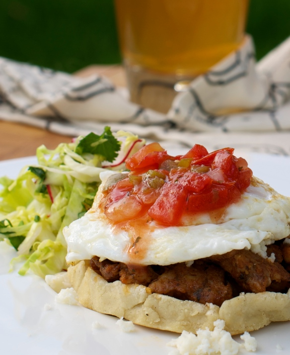 Breakfast Sopes topped with chorizo, a fried egg and salsa