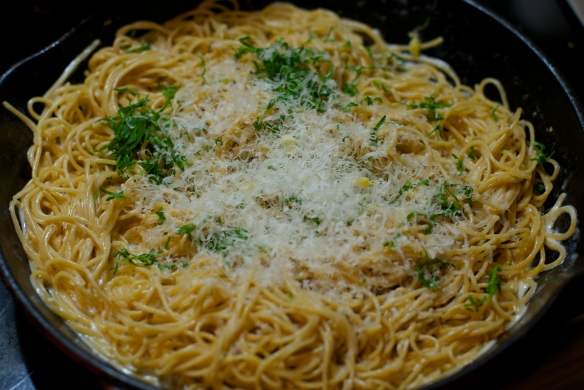 Pasta being tossed with reduced cream, butter and Parmesan