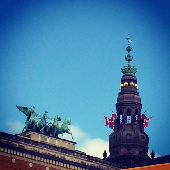 To the left, statues on top of the Thorvaldsen Museum. To the right, the spire of Christiansborg Palace.